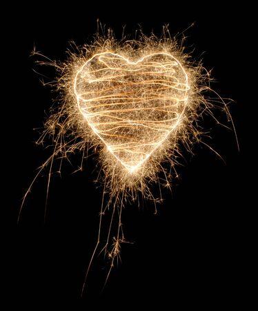 heart burn: SParkling heart made of fireworks on black background Stock Photo