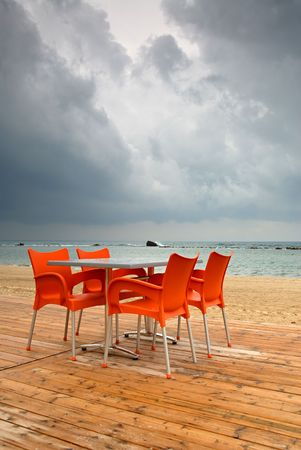 Rainy day at beach with empty cafe table on foregrund photo