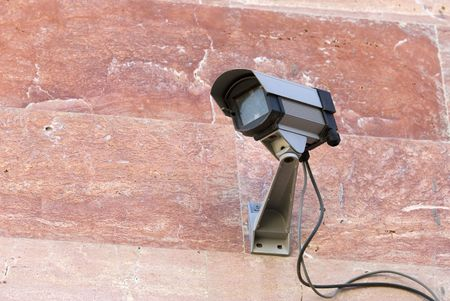 Security camera mounted on pink stone wall Stock Photo - 3232607