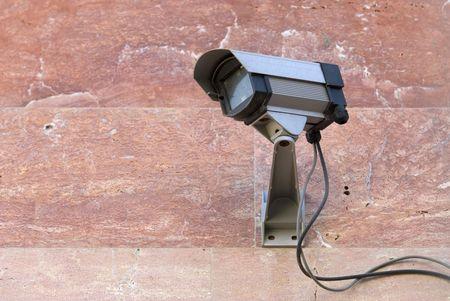 mounted: Security camera gemonteerd op de roze stenen muur