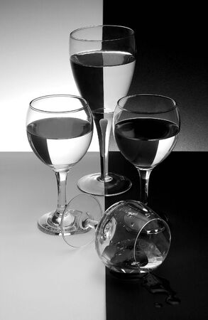 comrade: Three glasses standing guard on their fallen comrade on black and white background Stock Photo