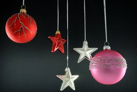 Hanging christmas tree ornaments on black background photo