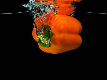 Orange pepper falling into water photo