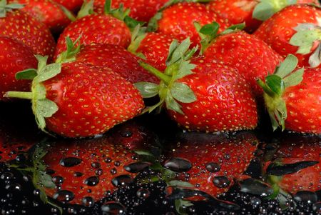 Fresh strawberries with water drops on wet black surface