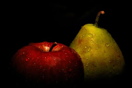 Wet red apple and green pear fading into black background