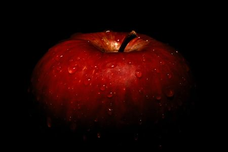 Wet red apple fading into black background Stock Photo