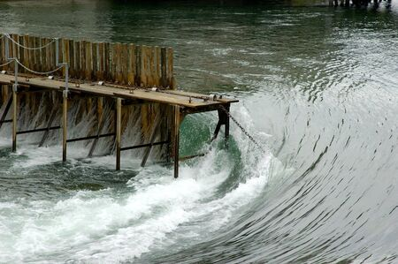 joa: Water power -water streaming around wooden damb Stock Photo