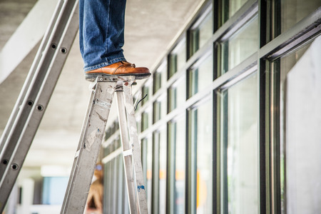 a man who was standing on the ladder by the leather shoes