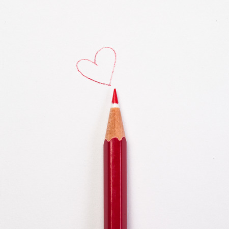 trait: Red pencil and a red heart Stock Photo