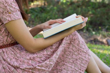 自然公園で聖書を読む若い女性
