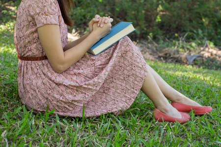 humbled: Young woman reading bible in natural park