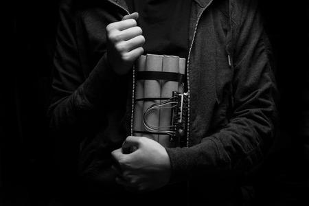 vrouw in een zwarte jas vastgebonden met explosieven en ontsteker houdt in haar hand Stockfoto
