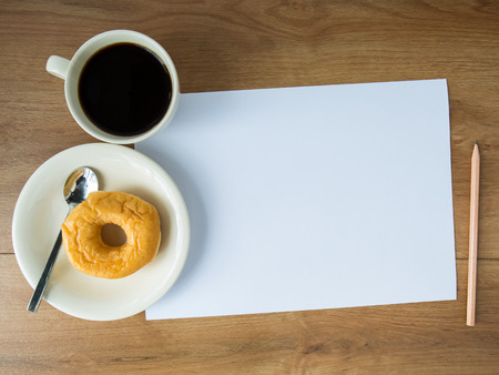 blank paper with coffee cup and donut and note and pencil on wooden background photo