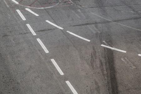 road surface: Intersection symbol on a black asphalt road surface.