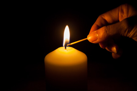 candles: hand with matchstick, lighting a candle Stock Photo