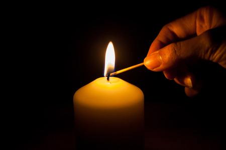 candela: mano con fiammifero, accendere una candela Archivio Fotografico