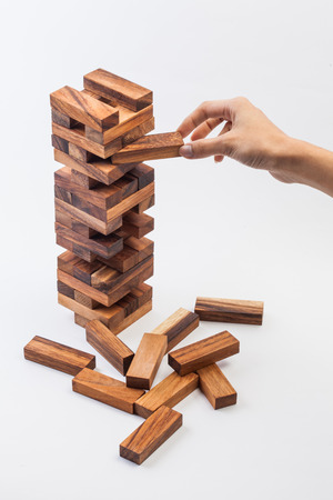 Hand spelen met het hout spel (Jenga). op een witte achtergrond.