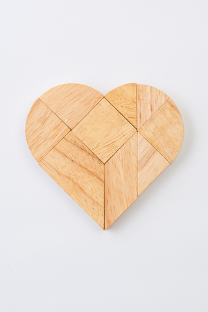 parallelogram: heart version of tangram, a traditional Chinese Puzzle Game made of different wood parts to build abstract figures from them, isolated on white