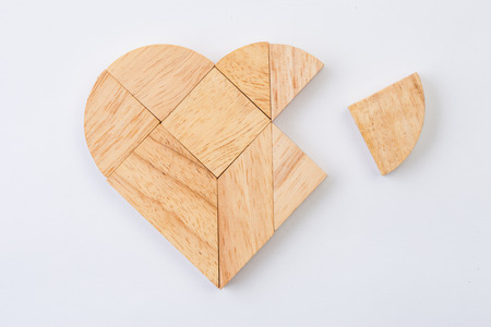 brainteaser: heart version of tangram, a traditional Chinese Puzzle Game made of different wood parts to build abstract figures from them, isolated on white