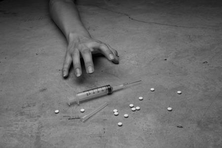 drogadiccion: Primer plano en el suelo de la jeringa con el medicamento. En el fondo, un joven drogadicto