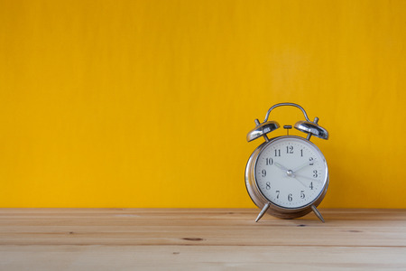 10 to 12 years old: Retro alarm clock on desk front yellow wall background Stock Photo