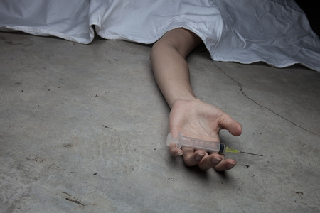 addiction alone: Close-up on the floor of the drugs in hand of the dead body. In the background, a young drug addict
