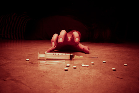 droga: Primer plano sobre el suelo de la jeringa con el medicamento. En el fondo, un joven adicto a las drogas, el color tono rojo procesada Foto de archivo