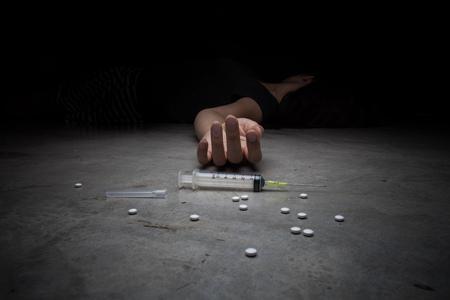 Close-up op de bodem van de spuit met het geneesmiddel. Op de achtergrond, een jonge drugsverslaafde