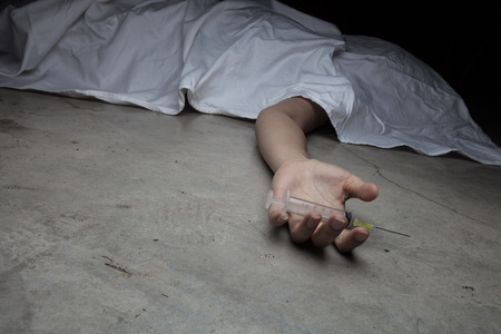 Close-up on the floor of the drugs in hand of the dead body. In the background, a young drug addict