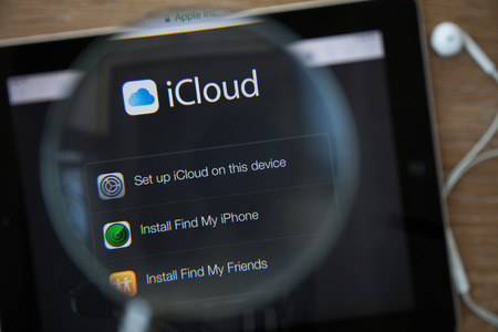 icloud: CHIANGMAI, THAILAND - February 26, 2015: Photo of Icloud homepage on a ipad monitor screen through a magnifying glass.