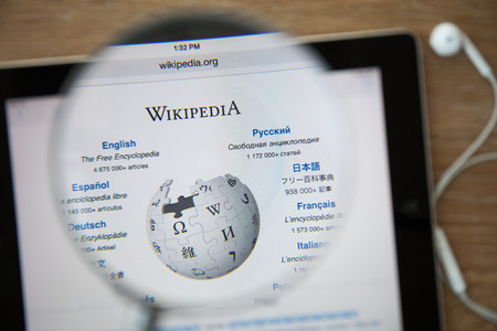 wikipedia: CHIANGMAI, THAILAND - February 26, 2015: Photo of Wikipedia homepage on a ipad monitor screen through a magnifying glass.