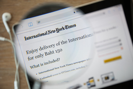 new york times: CHIANGMAI, THAILAND - February 26, 2015: Photo of the The New York Times homepage on a ipad monitor screen through a magnifying glass.
