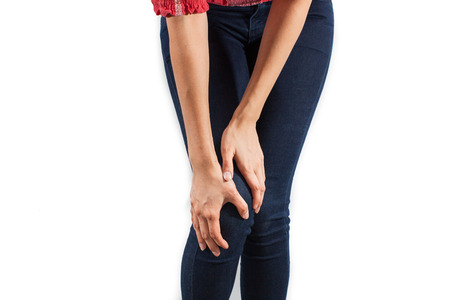 grouchy: Young, beautiful woman with knee-ache Stock Photo