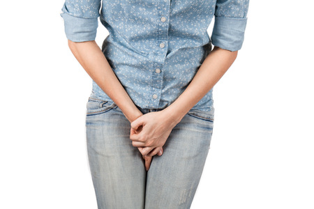 woman legs: Close up of a woman with hands holding her crotch isolated in a white background Stock Photo