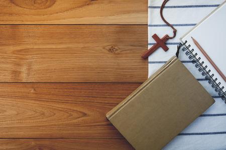 聖書木製テーブルの上に木製のクリスチャン クロスのネックレスのビンテージ トーン