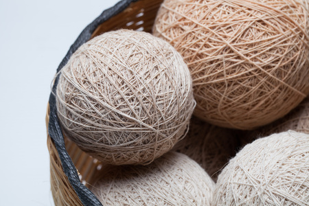 basket embroidery: balls of knitted wool in basket, closeup Stock Photo