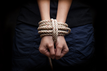 locked in: Hands of a missing kidnapped, abused, hostage, victim woman tied up with rope in emotional stress and pain, afraid, restricted, trapped, call for help, struggle, terrified, locked in a cage cell. Stock Photo