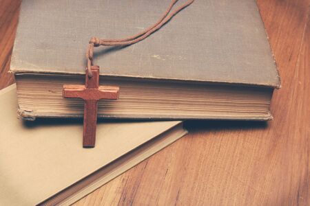 hymn: Vintage tone of wooden Christian cross necklace on holy Bible with copy space