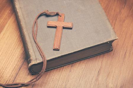 biblia: Tono de la vendimia del collar con una cruz cristiana de madera en la biblia santa con copia espacio