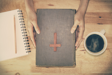 Tono de la vendimia de la cruz cristiana de madera en la Biblia durante la oración. Foto de archivo - 45595753