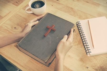 祈りの中に聖書のキリスト教の十字架を木製のビンテージ トーン。