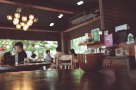 喫茶店のテーブルの上のコーヒー カップのビンテージ トーンは、ピンぼけ画像で背景をぼかし。