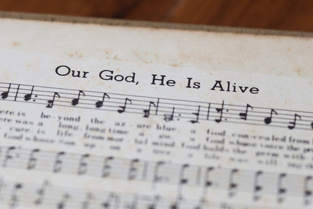 sheetmusic: CHIANGMAI, THAILAND, April 21,2015. Singing The Christian Hymnal book on the song of  Our God, He is alive  at home. April 21,2015