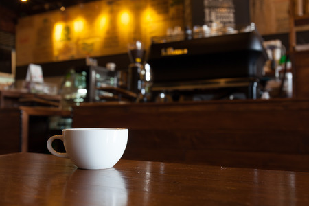 white cup of coffee on wooden bar in Coffee shop blur background with bokeh image . Archivio Fotografico