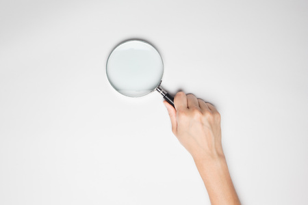 A female(woman) hand hold a magnifier(reading glass) isolated white at the studio. Standard-Bild
