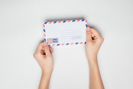 letter envelopes: Una mujer (mujer) asimiento de la mano un sobre blanco aislado en el estudio.