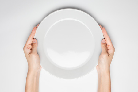 dinner plate: Female(woman) two hands hold(support) a white dish(plate) isolated white and top view. Stock Photo