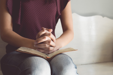 praying: Vintage tone of woman hands on bible. she is reading and praying over bible