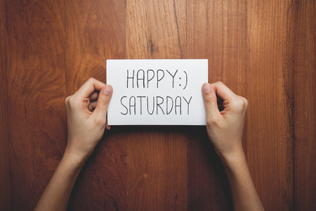 a woman with a sign in her hands with the words happy saturday