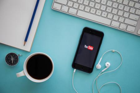 치앙마이, 태국 - 3 월 (17), 2016 브랜드 헤드폰 책상에 누워 화면에 YouTube 앱으로 애플 아이폰 6 새. YouTube는 인기있는 온라인 비디오 공유 웹 사이트입니